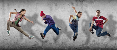 hip hop pose: Group of dancer in jump on cement background Stock Photo