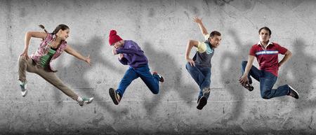 baile hip hop: Grupo de bailar�n en salto en el fondo de cemento