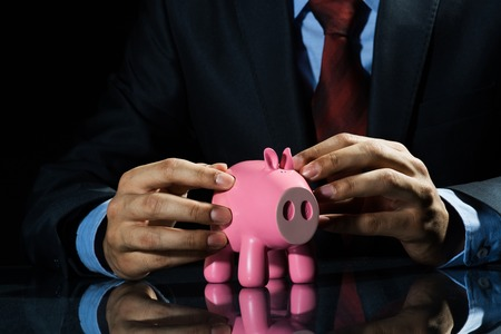Businessman holding pink piggy bank in hands photo