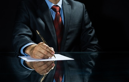 Close up of businessman sitting at table and signing document Archivio Fotografico