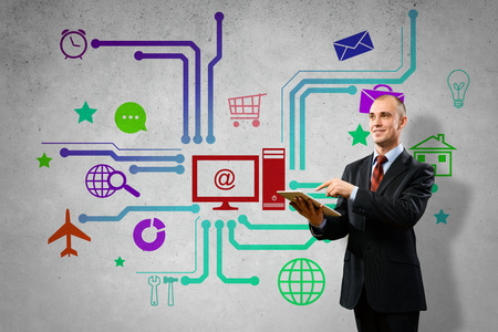 Businessman using tablet pc and color icons  photo