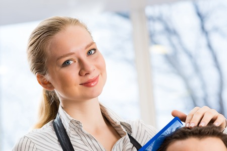 close portrait of a woman barber, hair puts the customer in the barbershop photo
