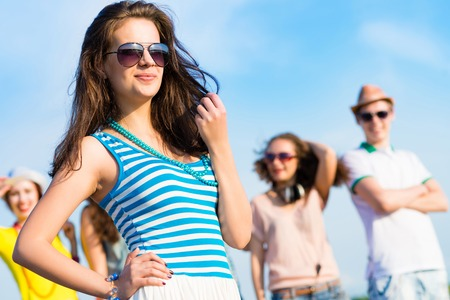 stylish young woman in sunglasses on the background of blue sky and friends photo