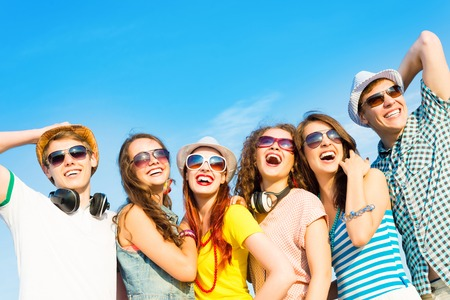 group of young people wearing sunglasses and hats hugging and standing in a row, spending time with friends photo