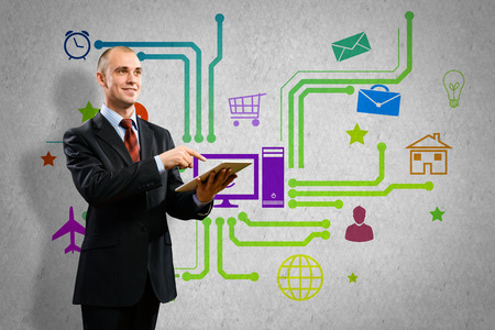 Businessman using tablet pc and color icons at background photo