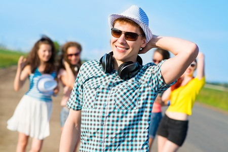 young man in sunglasses, a hat holds a hand on a background of blue sky and friends photo