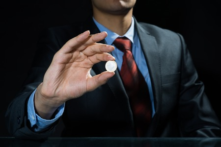 unpredictable: Close up of businessman holding coin in hand