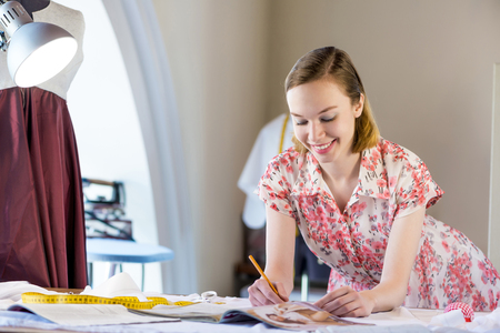 needlewoman: Young pretty needlewoman in studio working at order