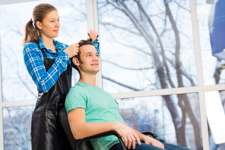 hair dresser: young attractive woman hairdresser hairstyle customer picks Stock Photo