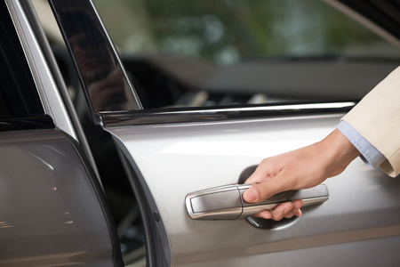 Close up of human male hand opening car door photo