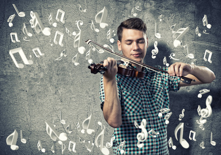 fiddlestick: Young man in casual on cement background playing violin