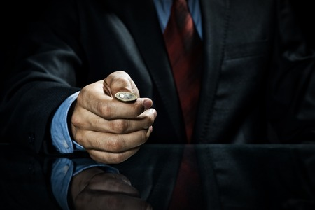 Close up of businessman holding coin in hand