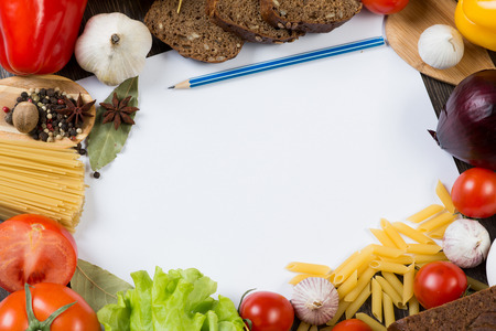 the recipe to write down: Set of vegetables and spices on kitchen table