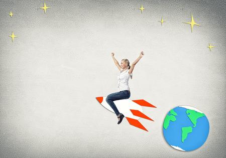 젊은 행복한 학생 소녀 타고 로켓 그리기