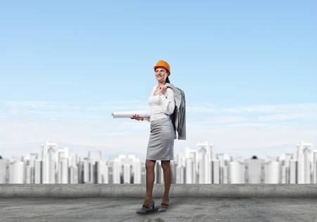 charismatic: Young woman architect in hardhat holding project in hand Stock Photo
