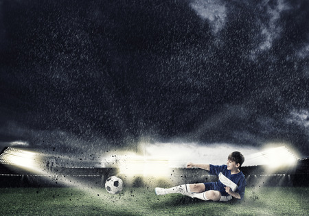 Opgewonden jongen voetballer bij stadion schoppen bal Stockfoto - 36663270