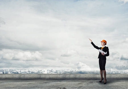 originator: Young woman architect in hardhat holding project in hand Stock Photo
