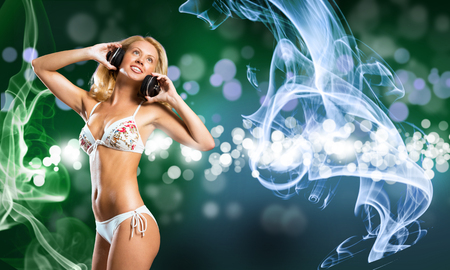Attractive girl in white bikini and headphones on color background photo