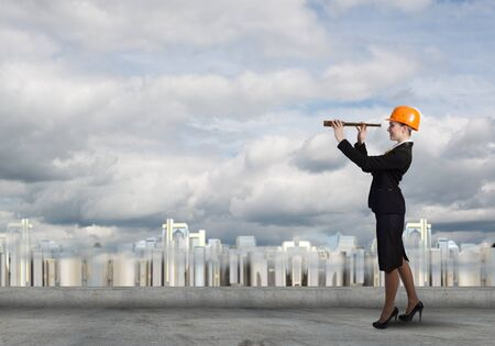 spy glass: Attractive woman engineer in hardhat looking in spy glass Stock Photo