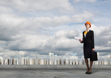Young woman architect in hardhat holding project in hand Stock Photo