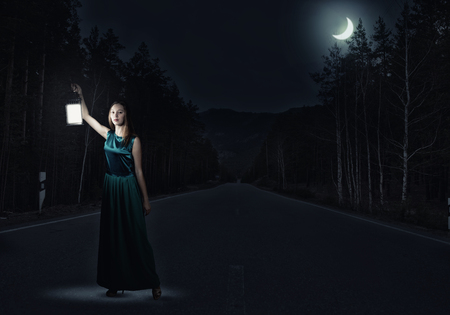 Young attractive woman in green dress with lantern walking in darkness Stock Photo
