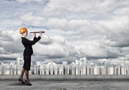 woman engineer: Attractive woman engineer in hardhat looking in spy glass Stock Photo