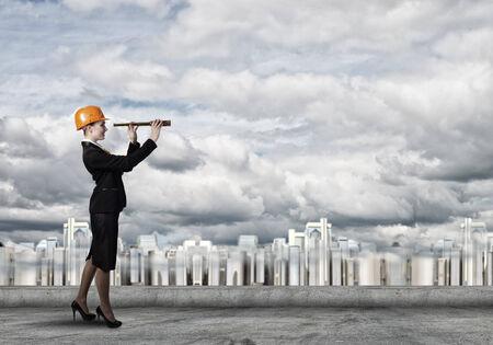 ingeniero: Ingeniero de la mujer atractiva en el sombrero duro que mira en catalejo