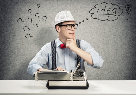 novelist: Young guy writer in hat and glasses using typing machine Stock Photo