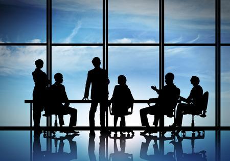 Silhouttes de la gente de negocios como equipo sentados mesa redonda Foto de archivo - 37617036