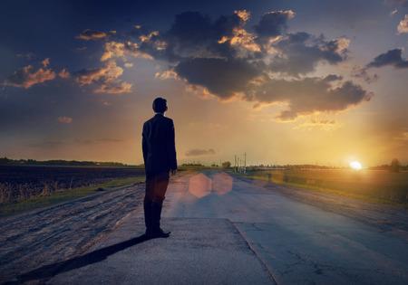 El hombre de negocios va directamente en su camino en la carretera de asfalto Foto de archivo - 37679552