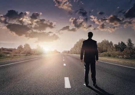 ビジネスマンは、アスファルトの道路に自分の道をまっすぐ行く