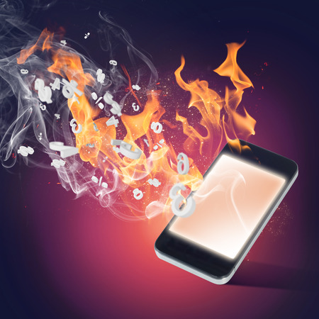 Conceptual image with mobile phone burning in flames photo