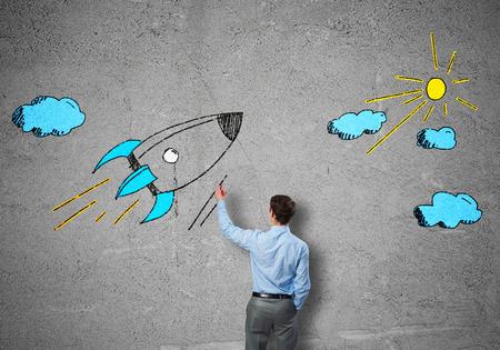 rocket man: Rear view of businessman drawing rocket on wall