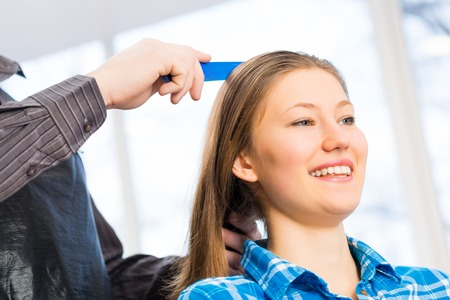 male hairdresser puts womans hair in a hairdressing salon photo