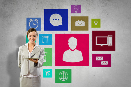 Businesswoman presenting tablet pc and color icons at background photo