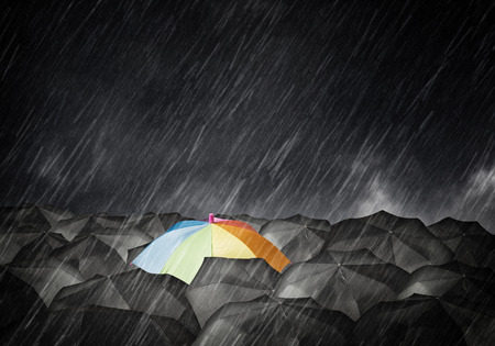 mainstream: Conceptual image with colorful umbrella among many black ones Zdjęcie Seryjne