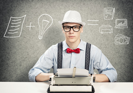 script: Young guy writer in hat and glasses using typing machine Stock Photo