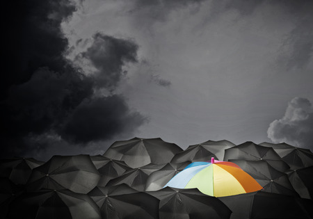 Conceptual image with colorful umbrella among many black ones photo