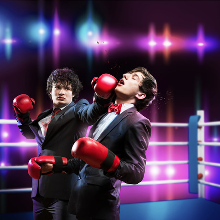 agression: Two businessman with boxing gloves in the ring fighting with each other