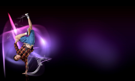 breakdancer: Young breakdancer performing a hand stand on color background