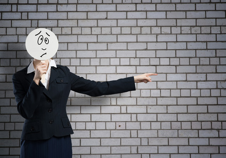 pessimist: Businesswoman hiding her face behind round banner with sad smiley