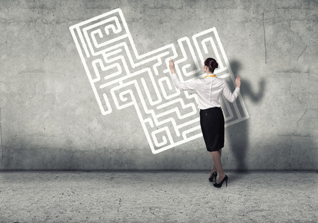 Back view of businesswoman drawing labyrinth on wall photo