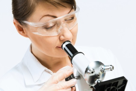 microscope slide: Attractive female scientist looking at the microscope slide in laboratory