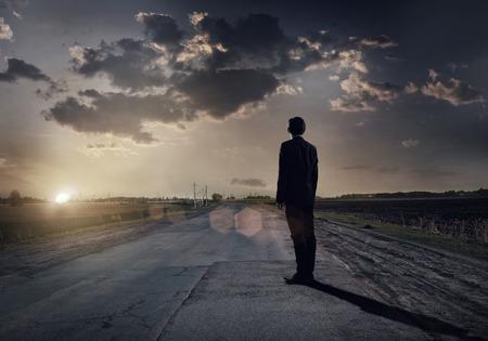mision: El hombre de negocios va directamente en su camino en la carretera de asfalto Foto de archivo