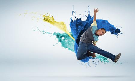 Junger Mann, der Hip-Hop Tänzer springt hoch