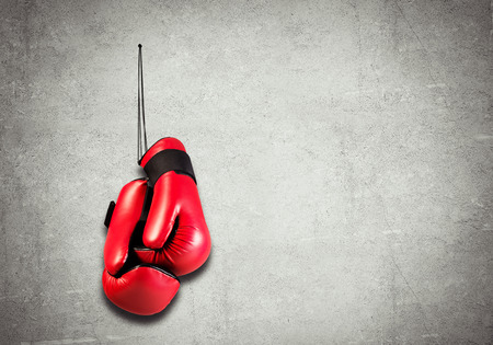 combative sport: Boxing gloves hanging nailed to wall as concept of retirement
