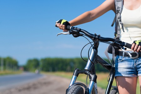 Unrecognizable young woman in shorts riding bicycle outdoors Stock Photo