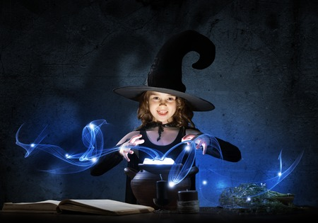 Little cute halloween witch reading spell above pot