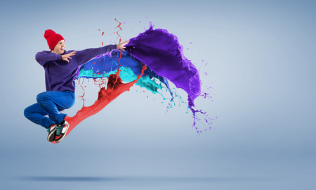 colorful paint: Modern styled dancer jumping over colorful paint splashes