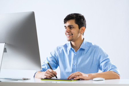 designer: Young graphic designer sitting at desk and working Stock Photo